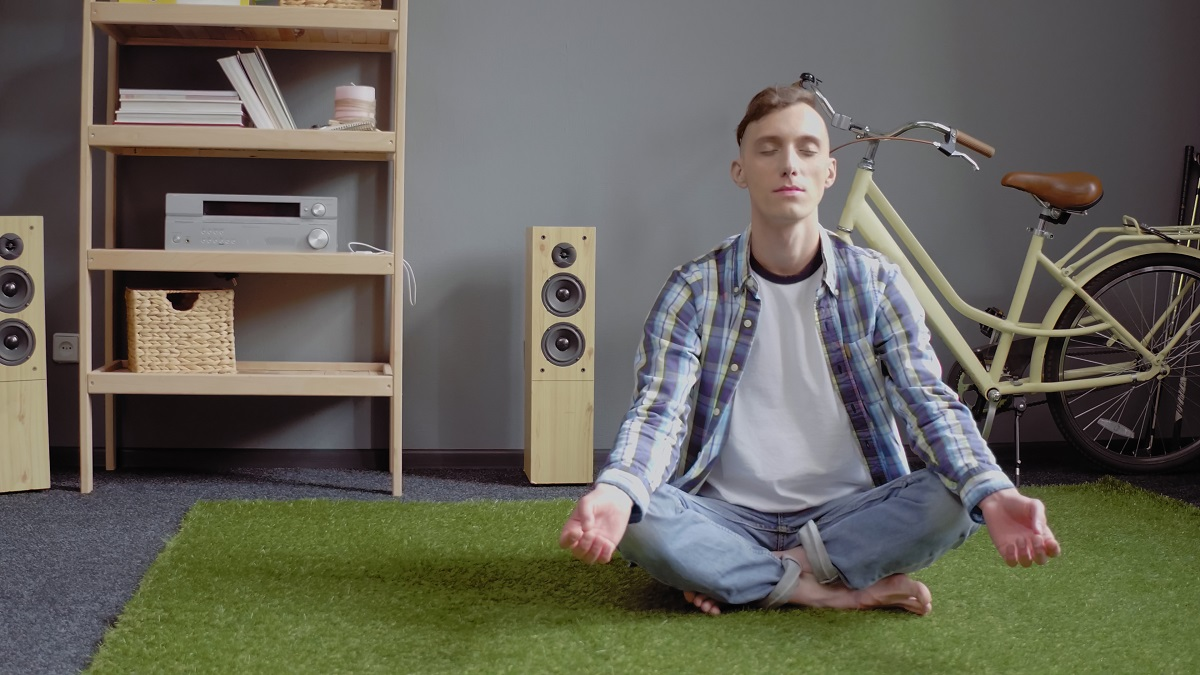 Caucasian man meditates resting closed eyes while sitting crossed legs on green carpet. Self-isolation at home. Quarantine concept. Toned image