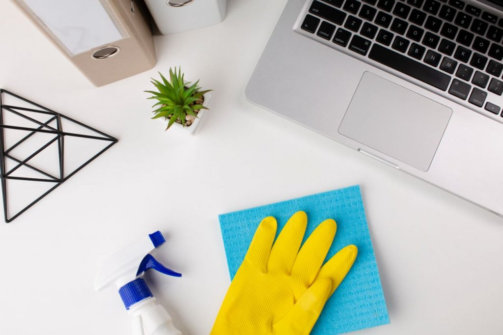 A person disinfecting an office desk