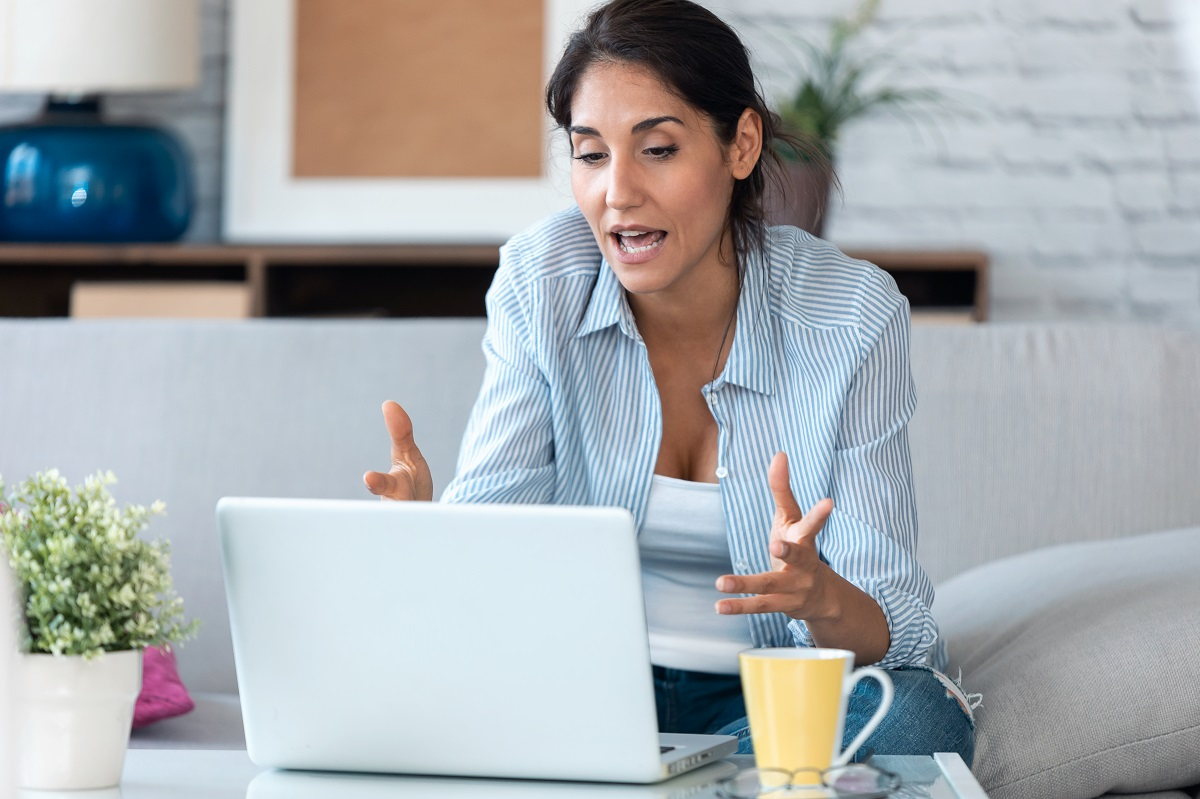 Business woman having online video call via laptop computer whil