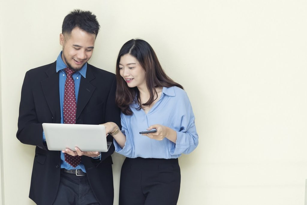Two Business People Working And Talking About Job With Mobile An