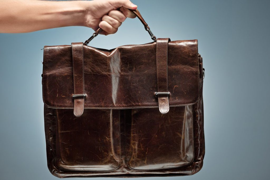 A man holding a brown leather travel bag